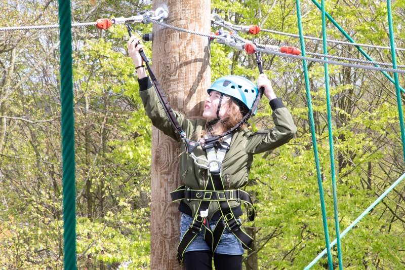 A photograph of a girl using the high ropes equipment